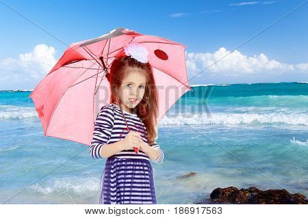 Beautiful little girl long hair and white bow on her head , in a summer dress in stripes.She stands under the umbrella.White sand , blue sea and blue sky with clouds.