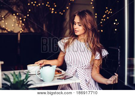 Beautiful elegant woman having breakfast drinking coffee and eating cake in city cafe.
