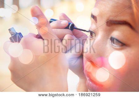Women are making up. Eye liner black. Have bokeh