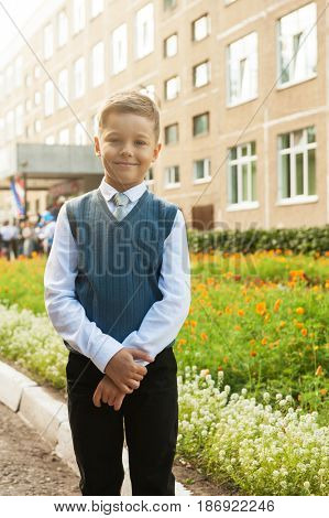 The first time in first class: happy schoolboy at school background
