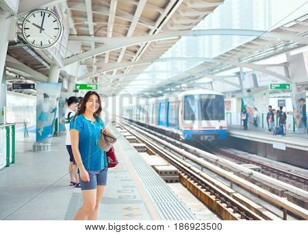 Beautiful biracial teen girl or young woman with shoulder bag standing on platform of train station in warm climate