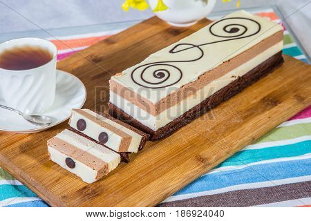 Three-layer chocolate cake, decorated with chocolate patterns. Background - porcelain cup with hot tea. Holiday cake Three-colate. Professional bakery