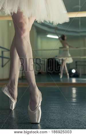 Ballerina in pointes and a pack warms up before the dance lesson. Crossed long slender female feet. Classical ballet. Prima ballerina. Shooting close-up.