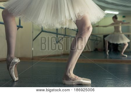 Ballet dancer in a pointe and a pack squats at the bench. Reflection in the mirror in the ballet class. Classical ballet. Prima ballerina. Shooting close-up.