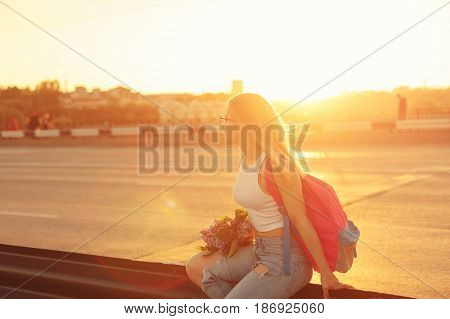 Young attractive hipster girl hitchhiking sits on the highway fence and holds a bouquet of lilac flowers. She is dressed in top and jeans. Backlight photography. Outgoing day and the setting sun.
