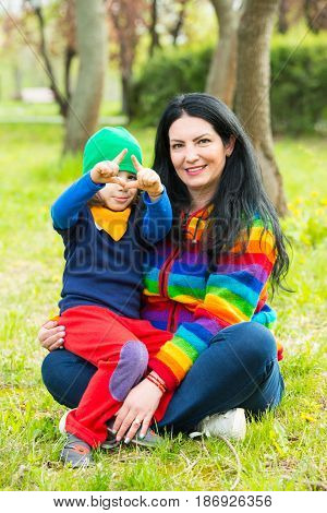 Mother and son sitting in grass in park and the boy showing sign fingers