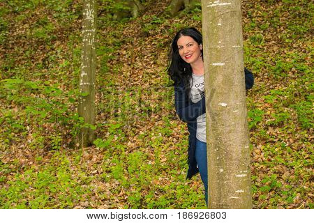 Woman is hiding behind the tree in the forest