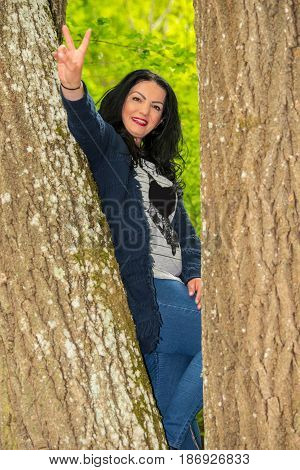 Woman ramped between trees showing victory fingers sign