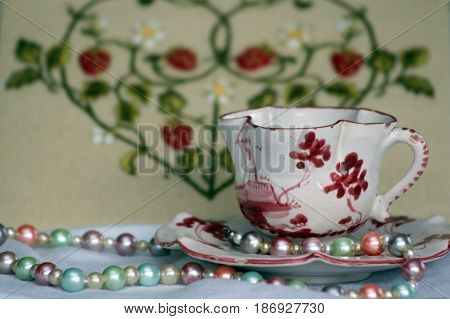 Antique teacup and saucer with pearl necklace and embroidered heart in background