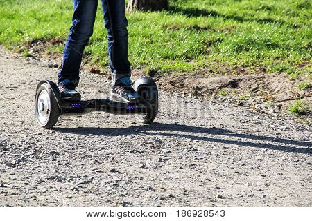 Legs of boy riding on self-balancing mini hoverboard in the city street. Electronic scooter outdoors - personal portable eco transport gyro scooter hyroscooter smart balance wheel mini segway
