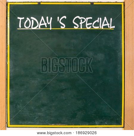 Blank advertising wooden chalkboard stands in front of restaurant for today's special menu.