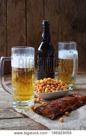 Football Fan Set With Mugs Of Beer, Bottle And Salty Snacks On Wooden Background. Junk Food For Beer
