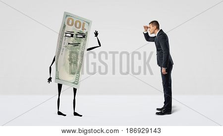 A businessman looking forward at a big money bill with arms and legs that is looking back at the man. Business results. Work evaluation. Total assets.