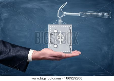 A businessman's hand turned up and a small silver safe standing on it below a drawn hammer on chalkboard background. Investment safety. Banking insurance. Credits and deposits.