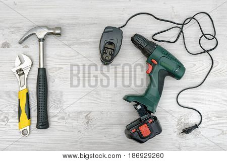 A cordless drill, it charger beside a hammer and a wrench on wooden table background. Handymen tools. Repair and renovation. Manual work and hobby.