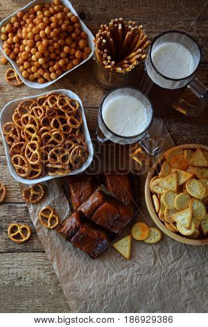 Football Fan Set With Mugs Of Beer And Salty Snacks On Wooden Background. Crackers, Pretzel, Salted