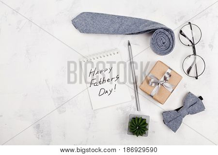 Happy Fathers Day background with notebook gift glasses necktie and bowtie on white table top view in flat lay style.