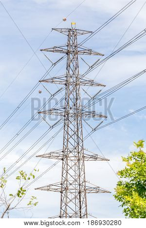 High voltage power pole and electricity line with blue sky background for power transmission.