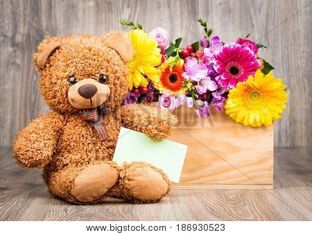 Flowers in the box and a teddy bear on wooden background