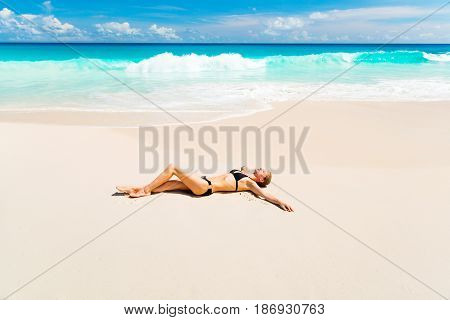 Photo of a young woman having rest on the beach