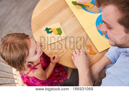 Teacher And Pupil Using Wooden Shapes In Montessori School