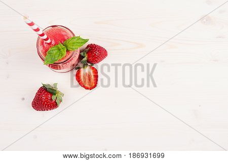 Freshly blended red strawberry fruit smoothie in glass jars with straw mint leaf cut ripe berry top view. White wooden board background copy space.