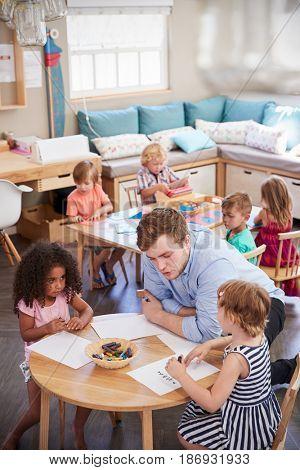 Teacher And Pupils Practicing Writing In Montessori School