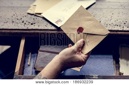 Human hand holding wax seal envelope correspondence