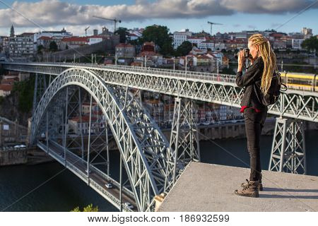 Traveller girl photographer with blonde dreadlocks is takes photo Dom Luis I bridge over Douro river, Porto, Portugal.
