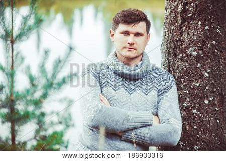 A man is standing in a wood near a tree in a jacket