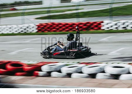 man drive go kart on track side shot