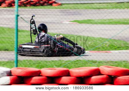 man drive go kart on track shot through  wire