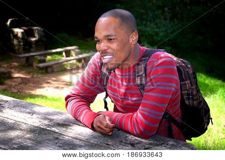Young black male wearing a backpack while sitting at a picnic table at a campground