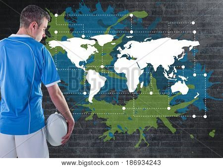 Digital composite of Rugby player holding ball next to Colorful Map with paint splatters on wall background
