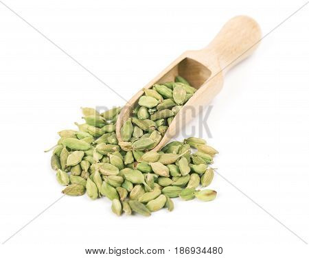 Cardamom seeds in wooden spoon isolated on a white background