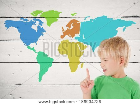 Digital composite of Boy pointing at Colorful Map with paint splatters on wood background
