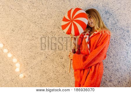 The horizontal photo of the teenager in the robe hiding behind the lollipop cushion and showing the tongue