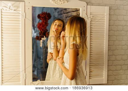 The reflection of the pretty smiling girl applying the lips in the mirror