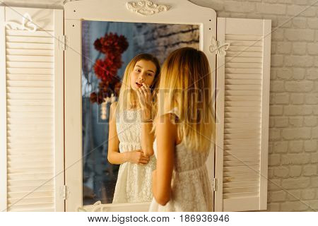The young teenager is applying the lips in the mirror. The close-up reflection.