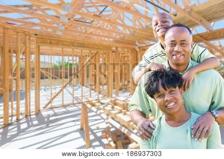 Young African American Family On Site Inside Their New Home Construction Framing.