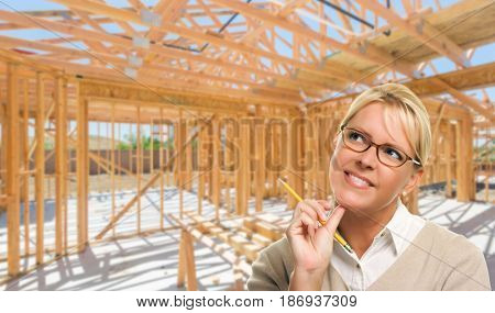 Pensive Woman with Pencil On Site Inside New Home Construction Framing.