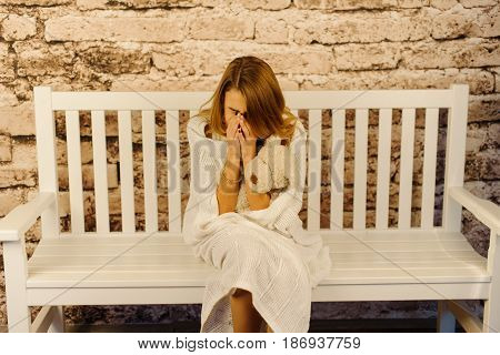 The crying teenager is wrapped in the knitted plaid while sitting on the bench
