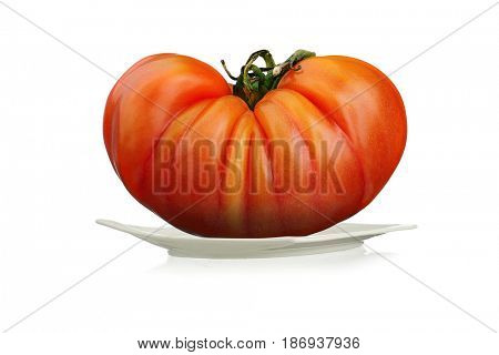 Extreme close-up image of German Heirloom tomato, served on plate studio isolated on white background
