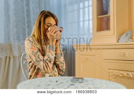 The young blond teenager is drinking tea while sitting on the chair