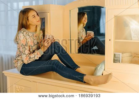 The horizontal photo of the dreaming young girl holding the cup of tea and sitting on the dressing-table