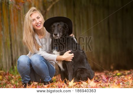 lifestyle outdoor portrait of young beautiful woman walking with black dog on natural background