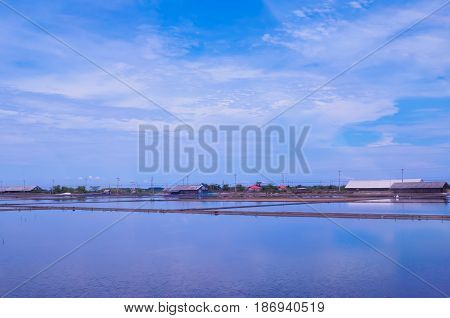 Salt field with shanty in panorama view with blue ocean color background. Feeling of being immense and lonely.