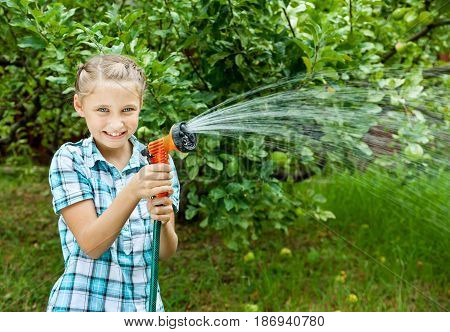 Happy girl pours water from hose watering flowers and grass