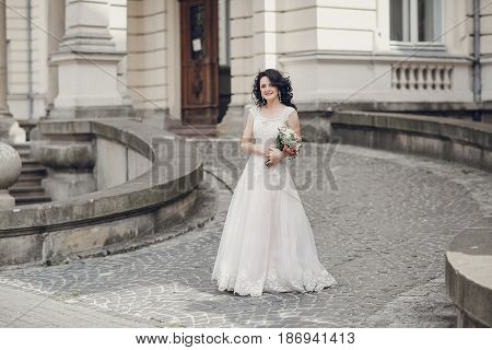 bride stands in the yard and in the background a big old house