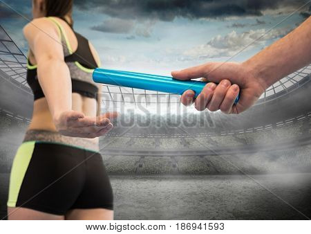 Digital composite of Hand with blue baton against stadium with flares